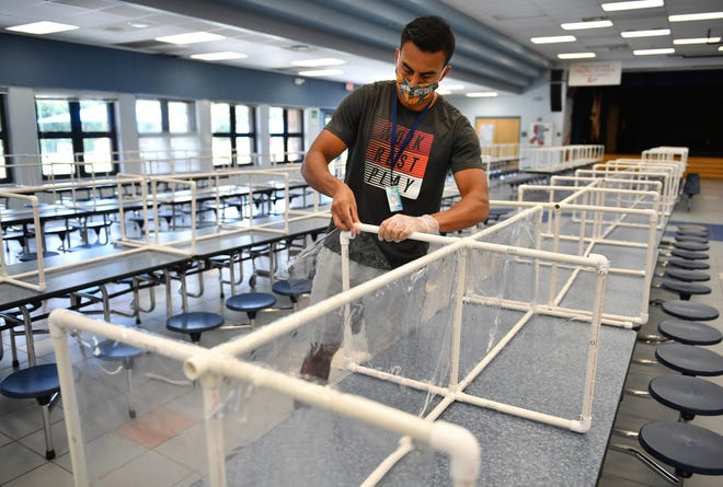 Ashton Elementary School physical education aide Elias Gutierrez slides a sheet of vinyl over a PVC frame in the school's cafeteria. As Sarasota County Schools prepare to open Monday, enrollment is even more of a wild card than usual.