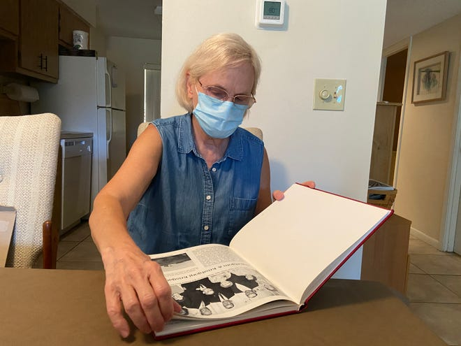 Maggie Kristjanson, 63, flips through a family photo and history book of her late husband's family. Ivan Kristjanson died May 16 from COVID-19. Support from Season of Sharing helped her in the aftermath.