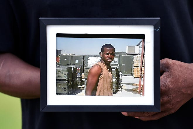 A family member holds up a photo of Adrian Jason Roberts at a vigil Aug. 20.