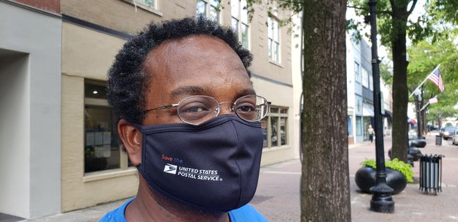 Myron Pitts wears a mask custom-made by Yellow Crayons, located in downtown Fayetteville.