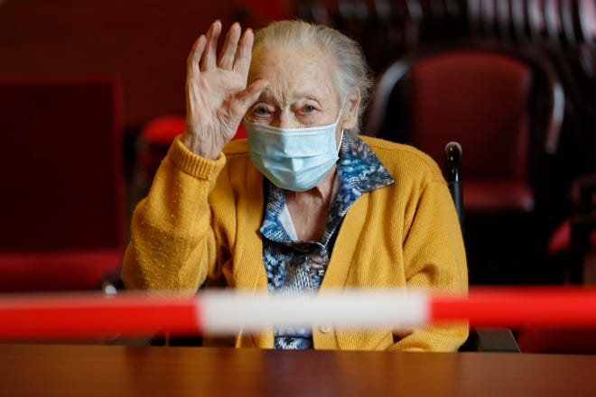 A women waves from a nursing home.