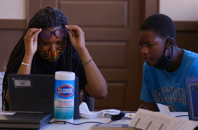 CHARLOTTE, North Carolina - On the first day of school Ty'reese Johnson, a freshman at Myers Park works through his computer challenges with Tijua Robinson, director of the Grier Heights Community Center.