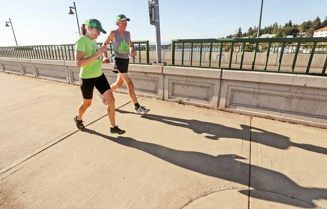 Tabatha Collins and friend Chris Lemke run down the sidewalk of the Manette Bridge in Bremerton on Thursday, Aug. 27, 2020.