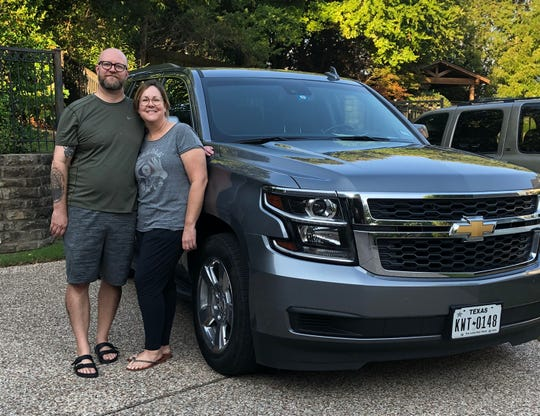 "Bruce Sperling and Kim Sperling of Dallas, Texas stand near the 2018 Chevrolet Suburban that they escape in for ""day dates"" each Sunday since the coronavirus pandemic started. Studies show many Americans use their cars as retreats from home confinement."