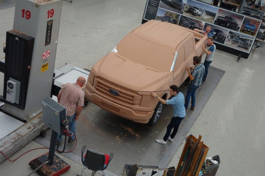 Ford designers work on a clay model of the 2021 F-150 at the Dearborn Product Development Center design studio in 2018. Senior designer Josh Henry is pictured in the blue shirt near the front headlight.