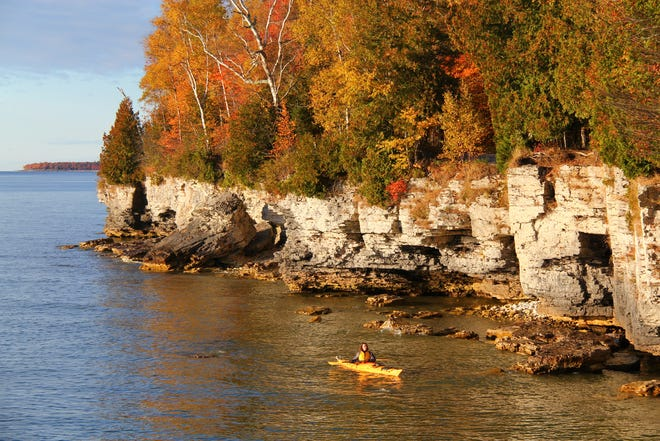 A kayaker paddles along the fall-colored shoreline at Cave Point County Park, one of Door County's popular nature attractions.