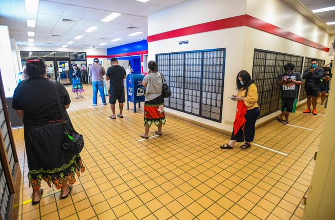 Patrons wait in a long line winding through the interior of the U.S. Postal Service's John Pangelinan Gerber Post Office Building in Barrigada on Friday, Aug. 28. 2020.