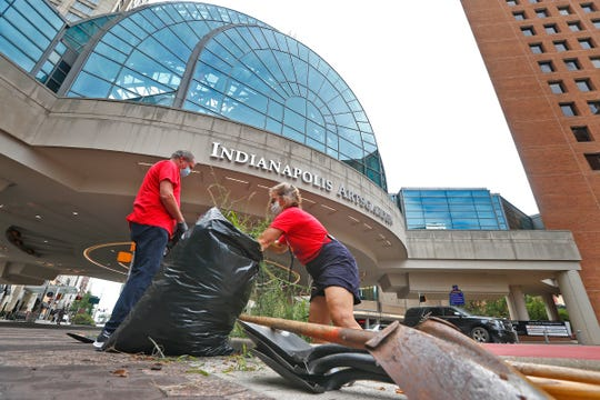 """Employer Wellness Solutions CEO Jennifer Sanner cleans up weeds on Washington Street, as civic and local leaders gather to beautify downtown, Friday, Aug. 28, 2020. Beautification is part of the """"Back Downtown"""" message."""