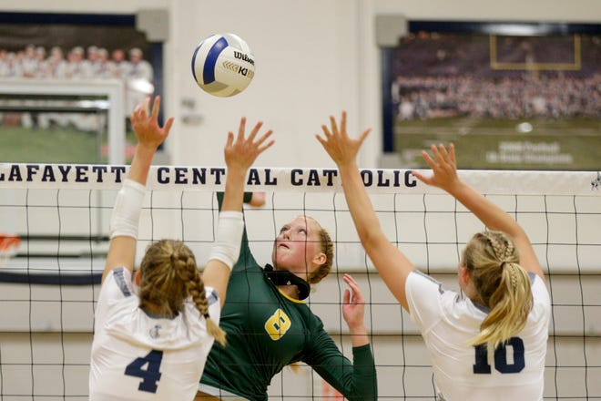Benton Central's Lilly Cobb (8) goes up for a hit as Central Catholic's Lydia Baker (4) and Central Catholic's Grace Roach (10) go up to block during the second set of an IHSAA volleyball game, Thursday, Aug. 27, 2020 in Lafayette.