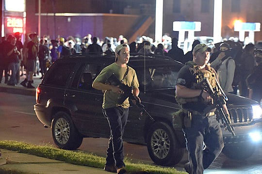 Kyle Rittenhouse, left, walks along Sheridan Road in Kenosha, Wis., on Aug. 25, 2020 with another armed civilian. Prosecutors charged Rittenhouse, 17, from Illinois, in the fatal shooting of two protesters and the wounding of a third during a night of unrest after the police shooting of Jacob Blake.