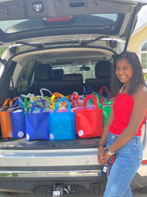 Anouska Prasad, who will be a senior at Muskego High School, is shown here with care packages for senior residents at Tudor Oaks Senior Living Community.