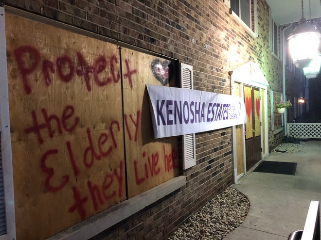 "Kenosha Estates windows are boarded up with a message saying ""protect the Elderly they live here."""