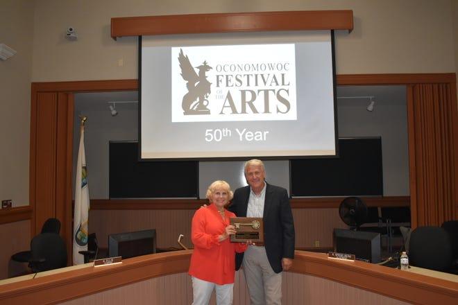 Oconomowoc Festival of Arts President Hollie Schick receives a key to the city from Oconomowoc Mayor Robert Magnus.