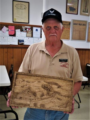 Don Clark holds a deep relief carving of a country home he recently displayed to the North Arkansas Woodcarver's Club. The Woodcarvers Club meets at 8 a.m. on Thursdays at VFW Post 3246 at the corner of 7th and Gray streets.