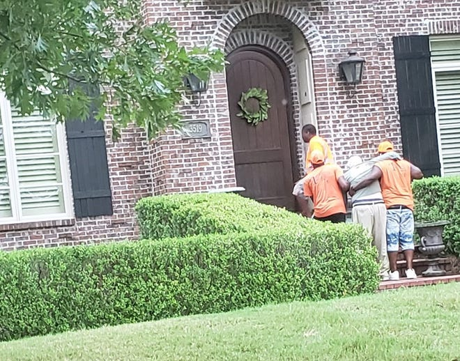 This photo provided by the city of Montgomery shows a sanitation crew helping a resident back to his home on Tuesday.