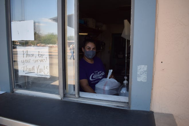 Waitress Dani Westfall spends her day taking orders and delivering them through a curbside pick-up window at Thai Delight de Mesilla Thursday, Aug.28, 2020.