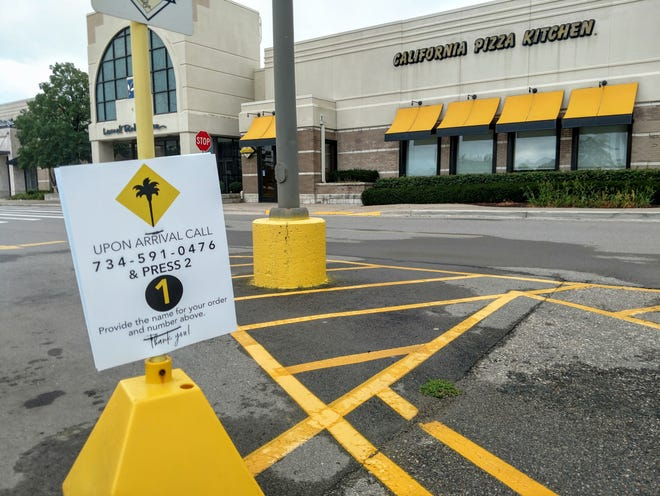 Curbside pickup signs are still zip-tied outside the California Pizza Kitchen Friday at Laurel Park Place in Livonia.