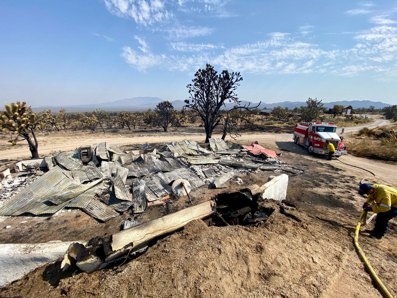 Firefighters work near a structure destroyed by the Dome Fire in the Mojave National Preserve.