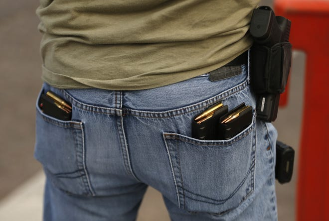 A pro-police supporter carries two guns and extra magazines in his back pockets during a weekly pro-police rally and Black Lives Matter counter protest in Gilbert on Aug. 27, 2020.