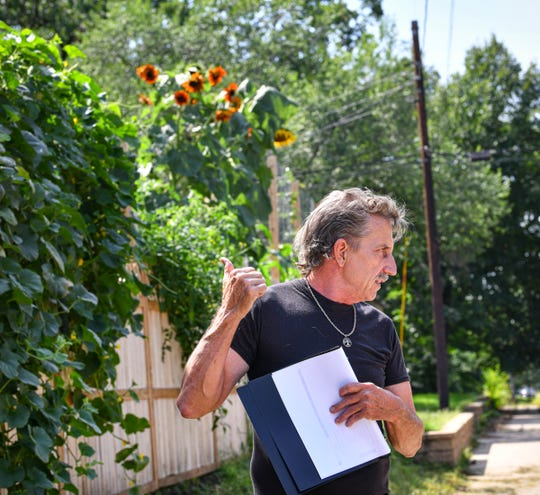 Curtis Wood talks about how he developed a growing system as sunflower plants tower above him Thursday, Aug. 27, 2020, at his home in St. Cloud.