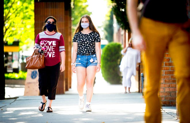 Rebecca Layton and her daughter Delaney Layton, both of Vancouver, Washington, wear face masks as they walk in downtown Provo, Utah, on Thursday, Aug. 27, 2020. (Isaac Hale/The Daily Herald via AP)