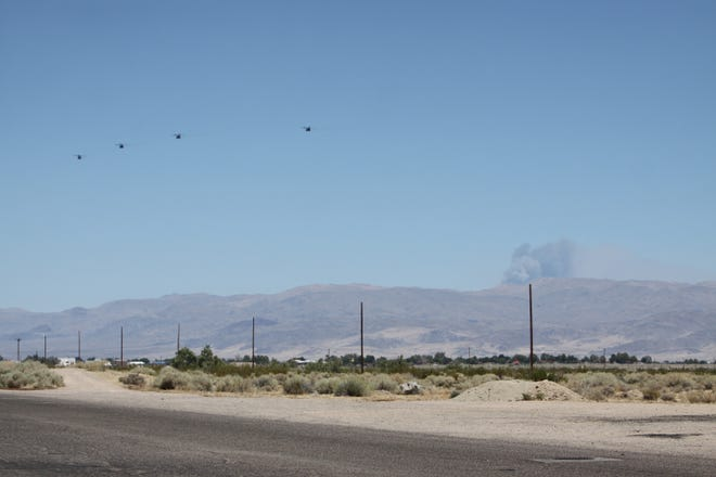Four helicopters head toward a plume of smoke from a fire located within the boundaries of Naval Air Weapons Station China lake on July 30.