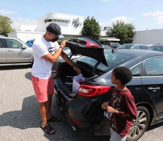 "Stephen Rodriguez and Carlton Rodriguez, 6, from Mount Vernon, place their shopping bag in their car, at the soon to be closed Lord & Taylor in Eastchester, Aug. 28, 2020. Says Rodriguez, ""I'm disappointed after almost 200 years of being open, they're closed. It's a landmark store for me, for shopping."""