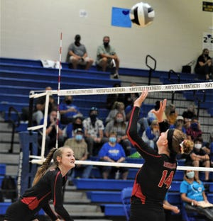 Coshocton's Jalynn West sets the ball for teammate Lindsay Bryant in Thursday's match against Maysville.