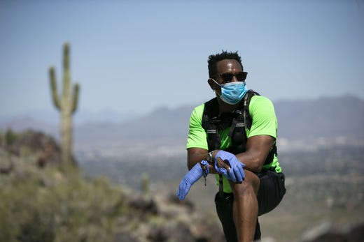 Wearing a mask and gloves because of the coronavirus pandemic, Byron Blades of Los Angeles, takes a rest, while hiking the trail up Piestewa Peak in the Phoenix Mountains Preserve on April 6, 2020.