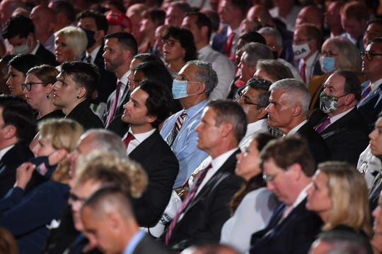 Few guests wear face masks as they watch from the White House South Lawn Thursday night as President Donald Trump delivers his acceptance speech for the Republican Party nomination for reelection.