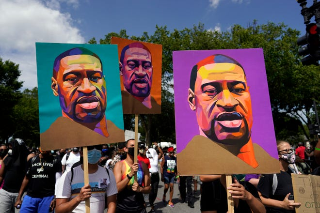 People carry posters with George Floyd on them as they march from the Lincoln Memorial to the Martin Luther King Jr. Memorial during the March on Washington, Friday Aug. 28, 2020, in Washington.