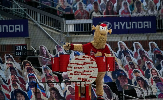 Atlanta Braves mascot Blooper tries to get a reaction from the cutout fans during the game against the New York Yankees during the fourth inning at Truist Park on Aug. 26.
