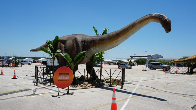 An apatosaurus welcomes visitors to the Jurassic Drive-Thru in Dallas. The exhibit that riders can safely view from the comfort of their vehicles is coming to the Greater Philadelphia Expo Center in Oaks Sept. 4-6 and Sept. 9-13.