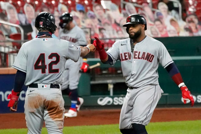 Cleveland Indians' Carlos Santana, right, is congratulated by teammate Francisco Lindor after hitting a two-run home run during the second inning of a baseball game against the St. Louis Cardinals Friday, Aug. 28, 2020, in St. Louis. (AP Photo/Jeff Roberson)