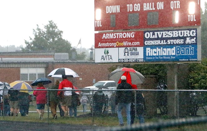 Fans head to their cars during a weather delay before the start of the Mapleton at Crestview high school football game at Crestview High School on Friday. The game was postponed until Saturday at 7 pm.