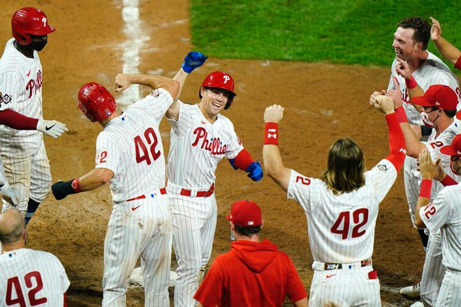 A smiling Scott Kingery celebrates with teammates after hitting a game-winning three-run homer off of Braves pitcher Mark Melancon during the 11th inning Friday night.