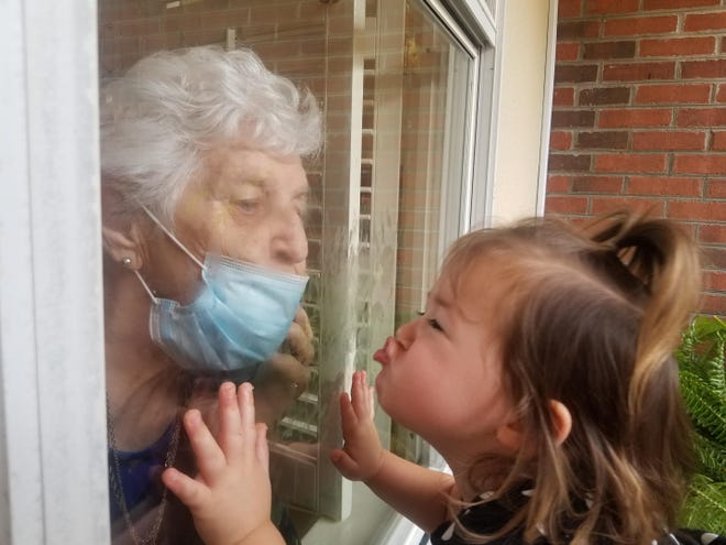 "Betty Bourgeois, 91, and great-granddaughter Jordan Pace, almost 2, share a ""social distance kiss"" through the window of Betty's room at St. Joseph Manor, an assisted living center in Thibodaux. Jordan is the granddaughter of Beth Bourgeois Pace of St. Francisville."