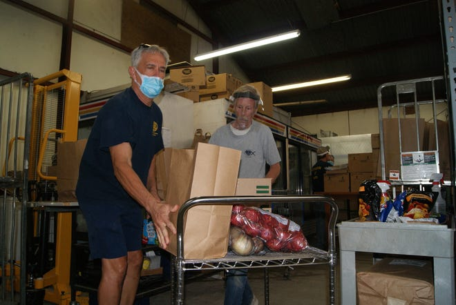 Paul Labat, Executive Secretary of the Houma Rotary Club, loads a bag of food on a cart being pushed by Matthew Clearwater at the Terrebonne Churches United Food Bank on Saturday.