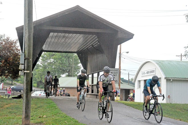 A group of cyclists start their ride by heading through the covered bridge at the Wayne County Fairgrounds at the Break the Cycle event.