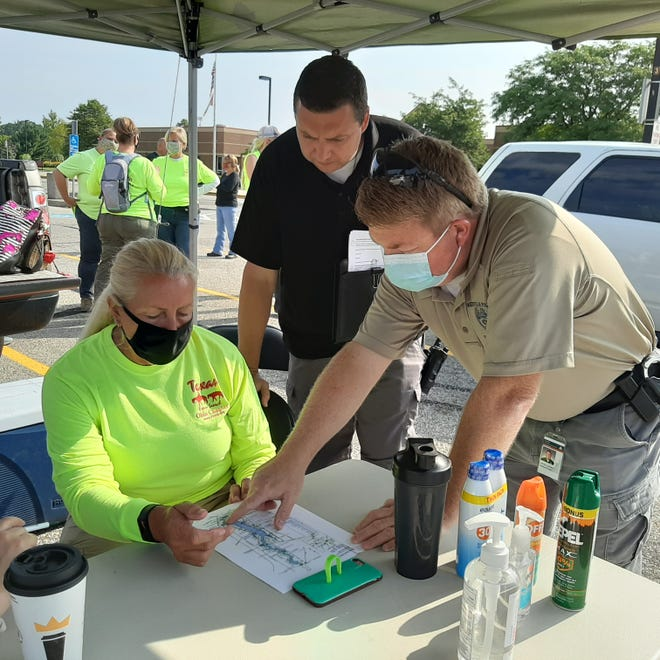 Linda Bommer, search coordinator with the Midwest Chapter of Texas EquuSearch, goes over a map of Alum Creek with Westerville Police Detective Steve Grubbs (center) and Sgt. Justin Alloway as they prepared to lead volunteers in a search on Aug. 16 to look for Emily Noble, who has been missing from Westerville since late May.