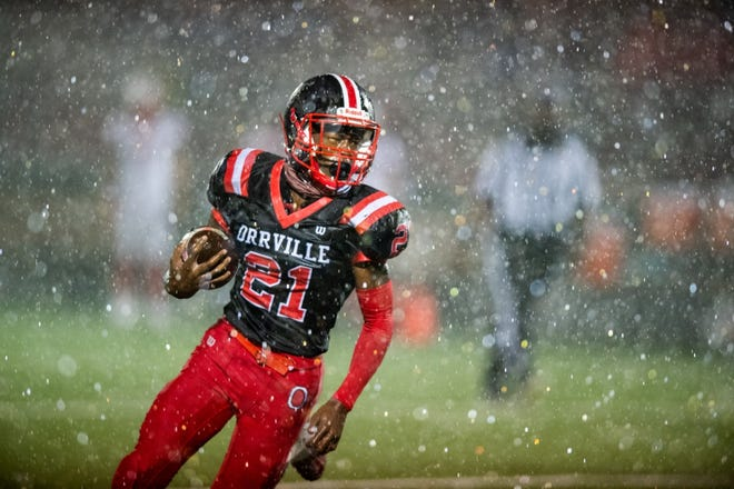 Orrville's Marquael Parks runs through heavy rain before the Riders' games against Northwest was postponed.