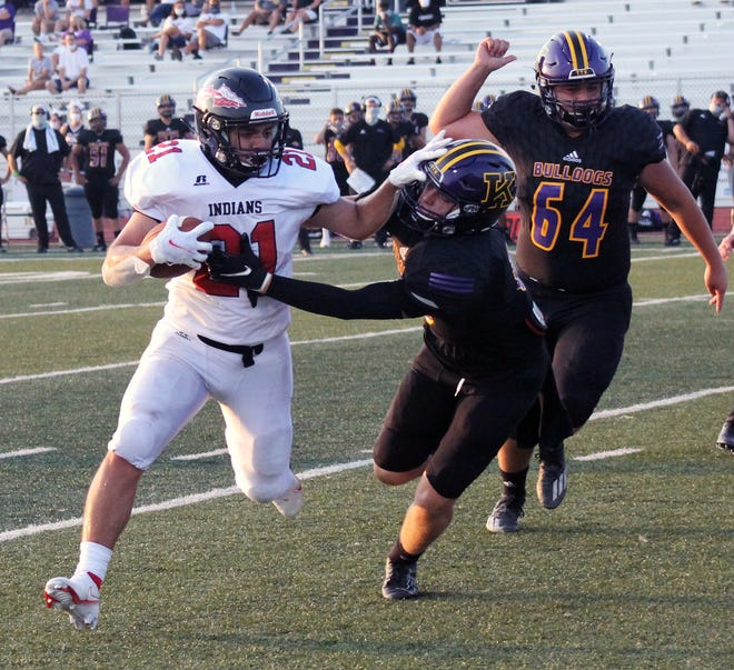 Fort Osage running back Corey Olvera (21) stiff-arms a Kearney defender in Friday's season opener at Kearney. The Indians fell to the Bulldogs 27-21 in overtime.