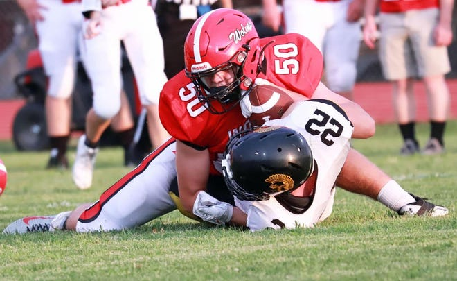 Winfield-Mount Union's Chance Malone (50) stops the run of Tri County's Dylan Icenbice Friday at Winfield.