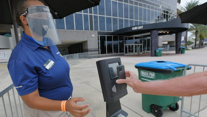 Guest Services worker Lyllian Blackshear helps a fan with a demonstration of the touchless ticket scanner at TIAA Bank Field on Saturday. Selected guests and members of the media were invited to the soft opening of the stadium with new accommodations made to help reduce the chance of spreading the coronavirus.