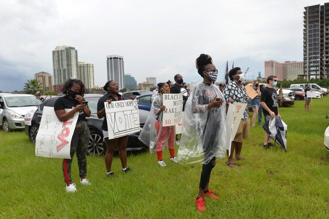 Braving the rain, crowds listen to speakers bat Saturday's  Northside Coalition and Jacksonville Community Action Committee Drive-In Protest to talk about the city budge and Black men and women being shot by police.