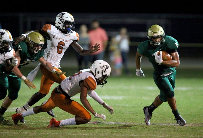 Fleming Island running back Timothy Thomas breaks free from Atlantic Coast defenders in a high school football game on Oct. 25, 2019. [Ralph Priddy/For the St. Augustine Record]