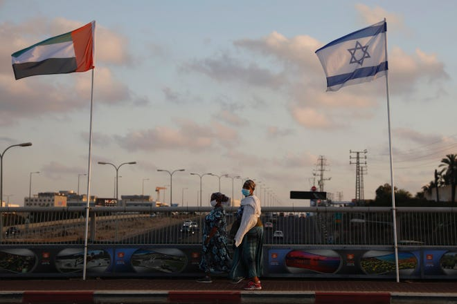 Women wearing face masks against the coronavirus walk past United Arab Emirates and Israeli flags at the Peace Bridge in Netanya, Israel, on Aug. 16. The UAE flag was displayed to celebrate last week's announcement that Israel and the United Arab Emirates have agreed to establish full diplomatic relations.