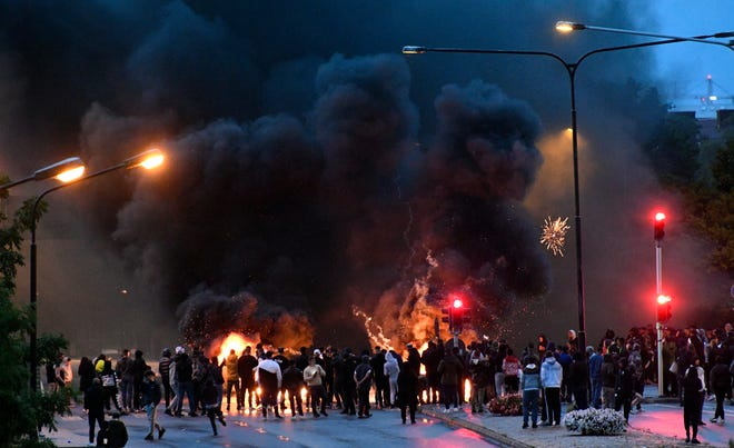 Smoke billows from burning tyres and pallets and fireworks as a few hundred protesters riot in the Rosengard neighbourhood of Malmo, Sweden, on Friday. Far-right activists burned a Quran in the southern Swedish city of Malmo, sparking riots and unrest after more than 300 people gathered to protest, police said Saturday. Rioters set fires and threw objects at police and rescue services Friday night, slightly injuring several police officers and leading to the detention of about 15 people.