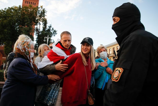 Women try to defend a protester as a police officer comes to detain him in Independence Square in Minsk, Belarus, on  Friday. The opposition is bracing for another big rally in Minsk on Sunday. Demonstrations around the capital's main square peaked to about 200,000 over the past two Sundays, the biggest protests the country has ever seen.