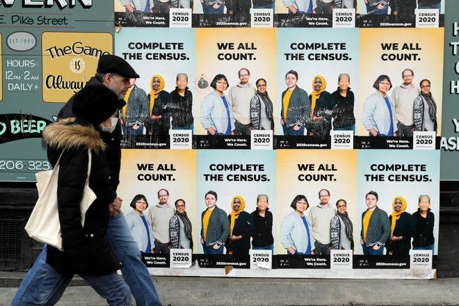 People walk past posters encouraging participation in the 2020 Census in Seattle's Capitol Hill neighborhood in April. The U.S. Census Bureau has spent much of the past year defending itself against allegations that its duties have been overtaken by politics.